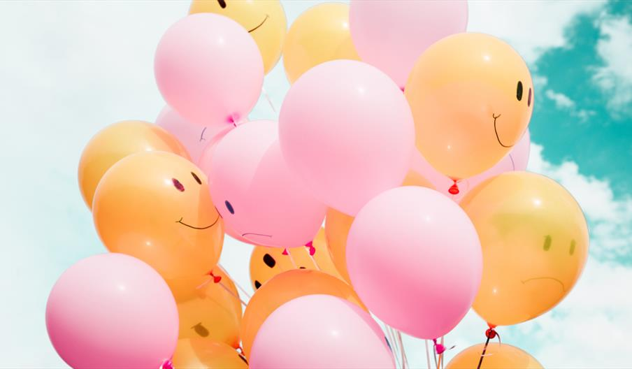 Yellow and pink balloons against a blue sky