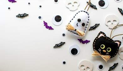 Felt ghost and black cat decorations surrounded by small bats and skulls