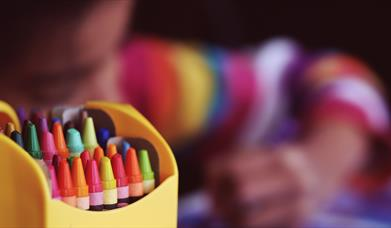 Yellow box of colourful crayons