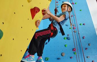 A child on the climbing wall at East Riding Leisure, Bridlington in East Yorkshire.