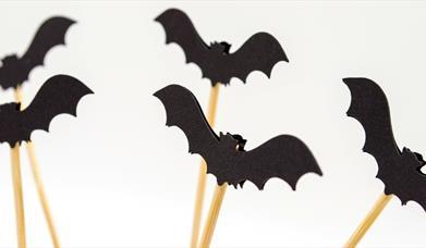 Black paper bats on wooden sticks
